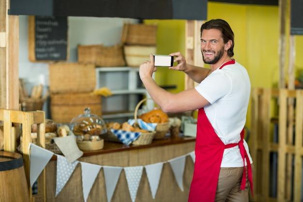 Porträt des bäckereipersonals, das bäckereisnacks und brot auf der theke fotografiert