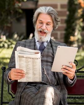 Porträt des bärtigen älteren mannes, der zeitung liest