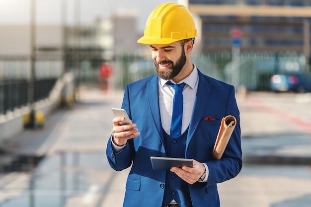 Porträt des bärtigen architekten in der formellen abnutzung unter verwendung des telefons und des haltens des projekts und des tablets, während auf der baustelle stehen.