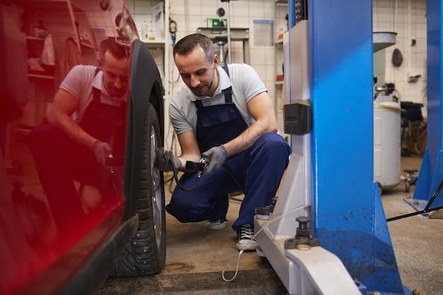 Porträt des bärtigen automechanikers in voller länge, der den druck in den reifen während der fahrzeuginspektion im garagengeschäft prüft, kopienraum