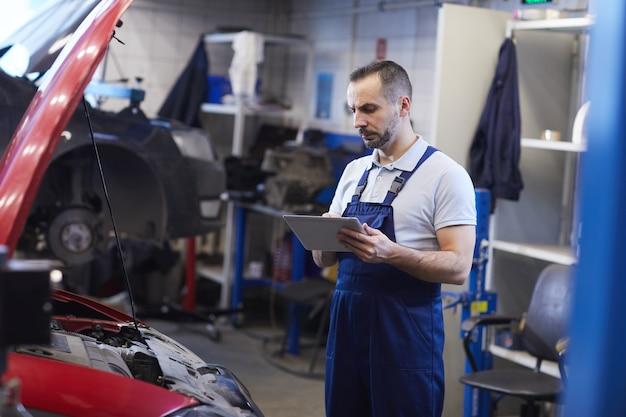 Porträt des bärtigen automechanikers unter verwendung des digitalen tabletts während der fahrzeuginspektion im garagengeschäft, kopienraum