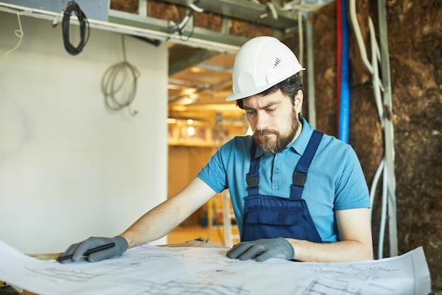 Porträt des bärtigen bauarbeiters, der helm trägt und grundrisse beim renovieren des hauses betrachtet, raum kopiert