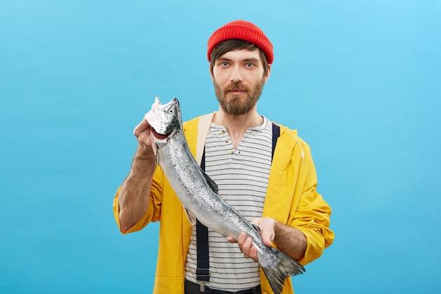 Porträt des bärtigen fischers, der mit großem fisch steht