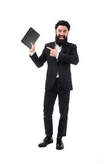 Porträt des bärtigen geschäftsmannes in voller länge mit tablette in der hand, mann zeigt auf leeren tablettbildschirm, lokalisiert auf weißer wand