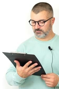 Porträt des bärtigen geschäftsmannkutschers, der brille mit mikrofon und zwischenablage trägt. mentor sprecher hält online-lektion