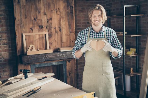 Porträt des bärtigen handwerkers, der in seinem holzgeschäft aufwirft