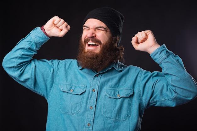 Porträt des bärtigen hipster-mannes, der sieg über schwarzen hintergrund feiert