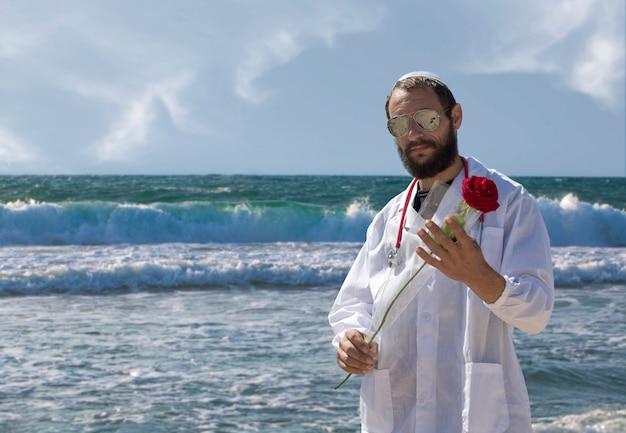 Porträt des bärtigen jüdischen arztes in weißer yarmulke (hut, kippah, jüdischer hut) mit sonnenbrille, mantel und stethoskop, die rote rosenblume in der hand hält. amerikanischer gutaussehender bärtiger mann auf seehintergrund