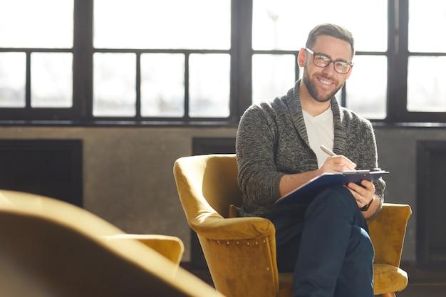 Porträt des bärtigen jungen geschäftsmannes in den brillen, die auf stuhl sitzen und lächeln, während notizen im dokument machen