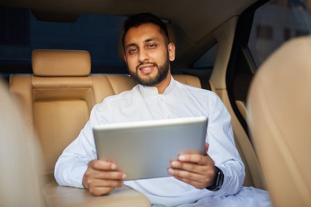 Porträt des bärtigen jungen mannes, der an der kamera lächelt, während digitales tablett im auto verwendet wird