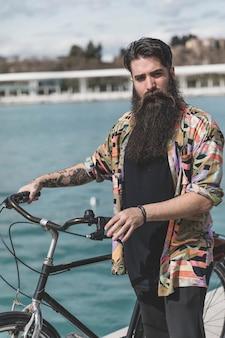 Porträt des bärtigen jungen mannes, der mit seinem fahrrad betrachtet kamera steht