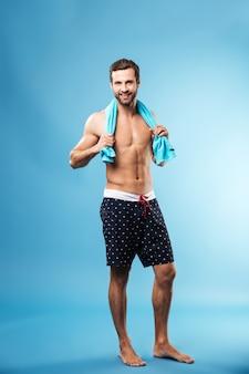 Porträt des bärtigen mannes, der über blau in der badebekleidung steht