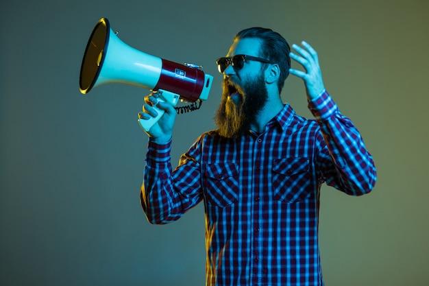 Porträt des bärtigen mannes des emotionalen hipsters mit megaphon auf weißem raum in der stilvollen sonnenbrille.