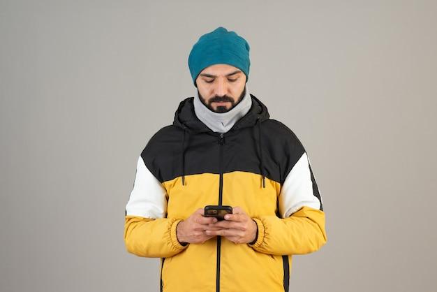 Porträt des bärtigen mannes in warmer kleidung, der sein handy gegen graue wand steht und hält.