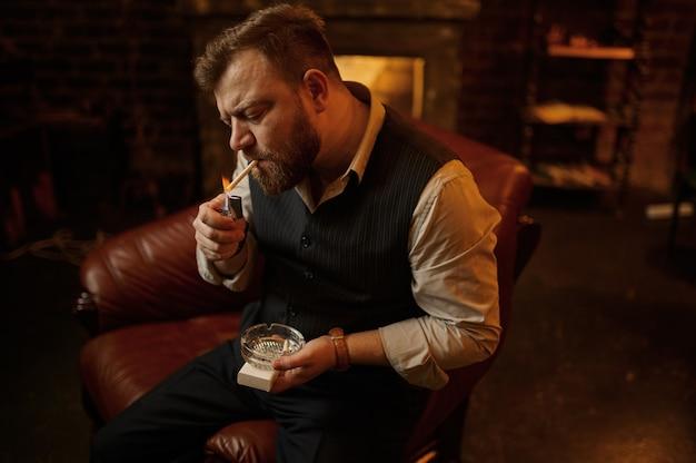 Porträt des bärtigen mannes mit aschenbecher zündet eine zigarette an, detailansicht. tabakrauchkultur, spezifischer geschmack. männliche raucher freizeit im büro
