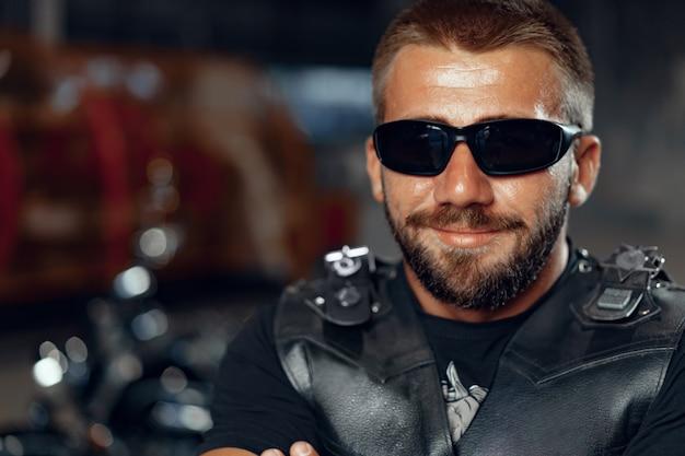 Porträt des bärtigen motorradfahrers in der dunklen sonnenbrille auf der dunkelheit