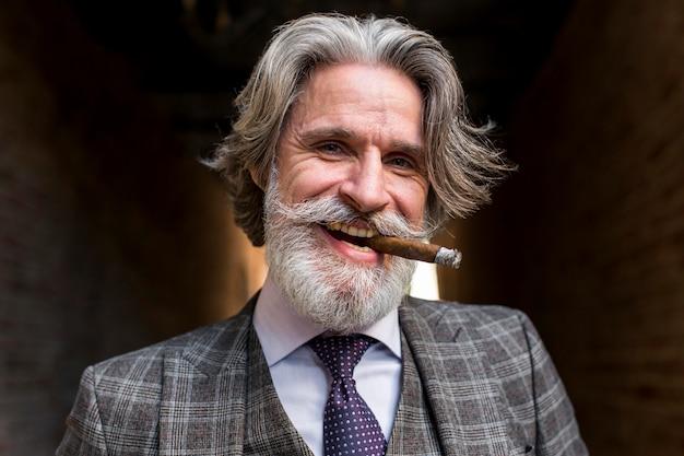 Porträt des bärtigen reifen männlichen rauchens