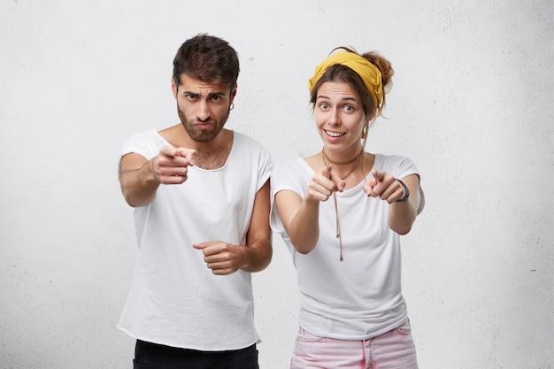 Porträt des bärtigen stilvollen mannes und der hübschen jungen frau, die freizeitkleidung trägt, die mit den fingern zeigt