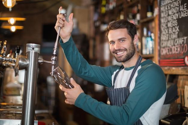 Porträt des barkeepers, der bier vom zapfhahn gießt