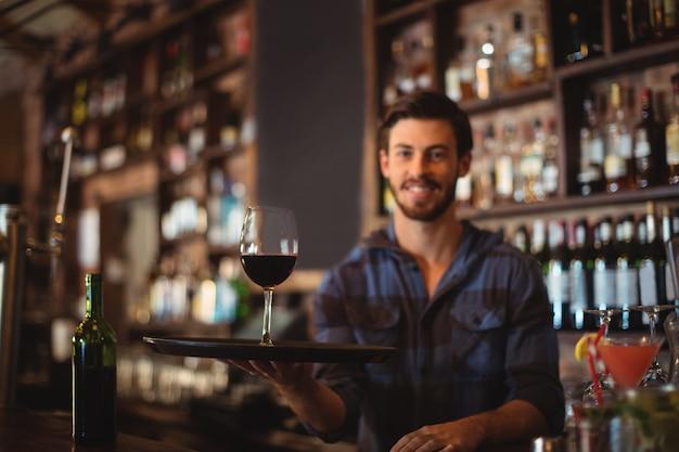Porträt des barkeepers, der ein tablett mit glas rotwein hält