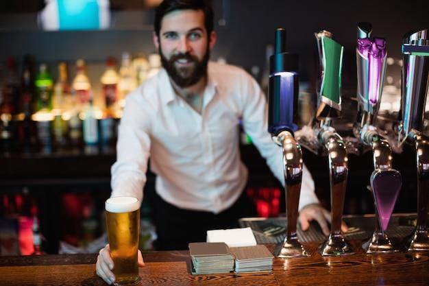 Porträt des barkeepers, der glas bier hält