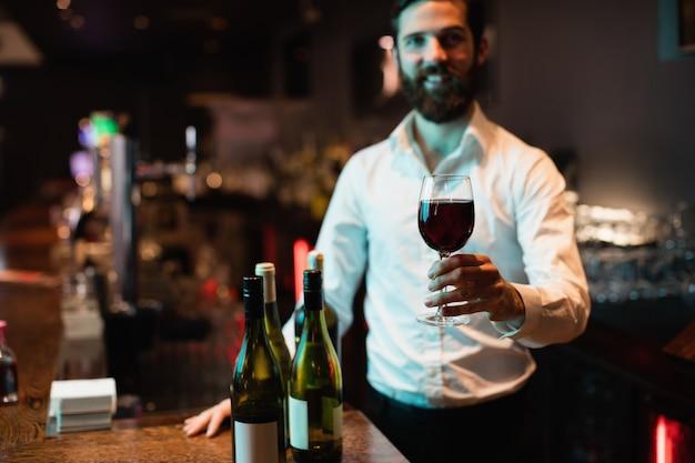 Porträt des barkeepers, der glas rotwein hält
