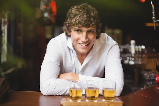 Porträt des barkeepers mit tablett mit whiskyschnapsgläsern an der bartheke