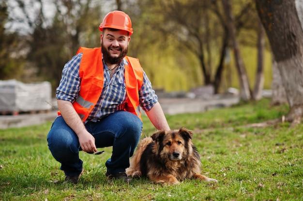Porträt des bartarbeitskraftmann-klagenbauarbeiters im orange sturzhelm der sicherheit mit wachhund.