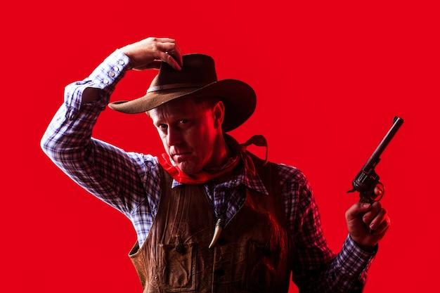Porträt des bauern oder des cowboys im hut. amerikanischer bauer. porträt des mannes, der cowboyhut, waffe trägt