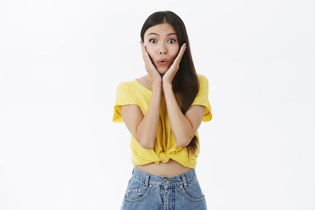 Porträt des begeisterten aufgeregten und faszinierten charmanten weiblichen shopoholic in den gelben trendigen t-shirt-faltlippen