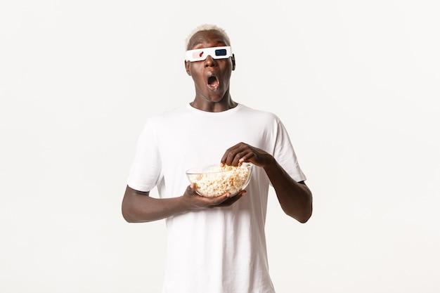 Porträt des begeisterten hübschen afroamerikanischen blonden kerls, der erstaunlichen film in den 3d-gläsern sieht, popcorn isst