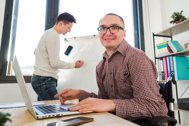 Porträt des behinderten mannes, der im büro arbeitet