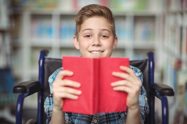 Porträt des behinderten schülers, der buch in der bibliothek hält