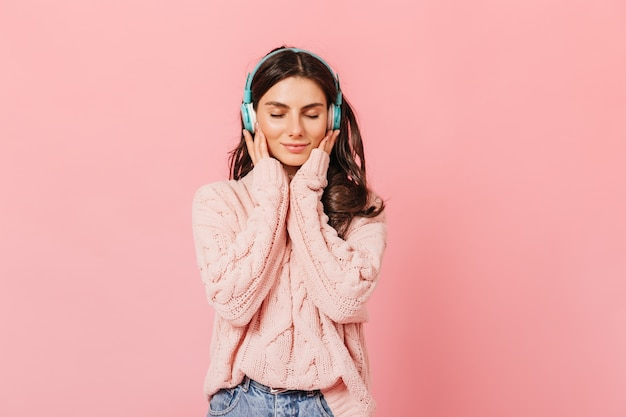 Porträt des beruhigten mädchens, das angenehme melodie in kopfhörern hört. dame im pullover niedlich lächelnd mit geschlossenen augen auf rosa hintergrund.