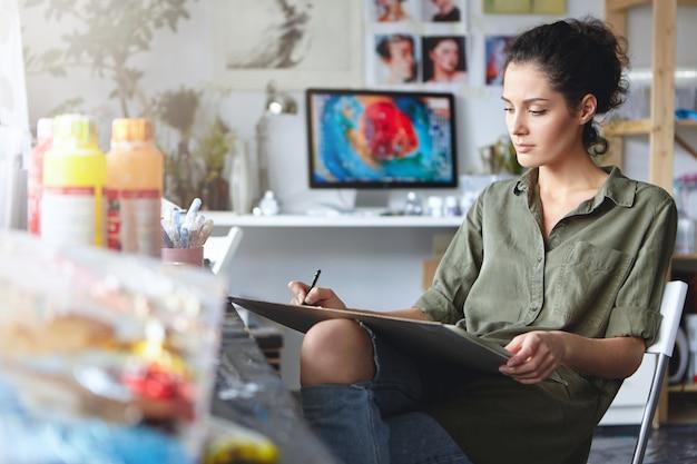 Porträt des beschäftigten selbstbewussten jungen brünetten frauendesigners in zerrissenen jeans, die an neuem kunstprojekt arbeiten und zeichnungen oder skizzen auf tablette machen. schöne künstlerin mit ihrer kreativen arbeit aufgenommen