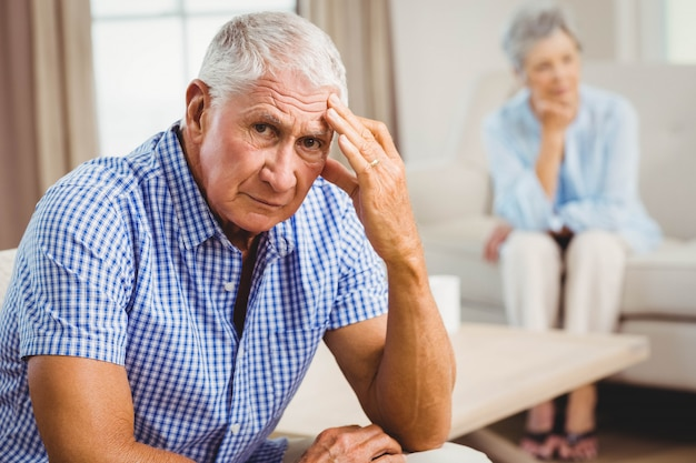 Porträt des besorgten älteren mannes, der auf sofa im wohnzimmer sitzt
