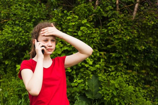 Porträt des besorgten hübschen mädchens, das auf mobiltelefon im park spricht