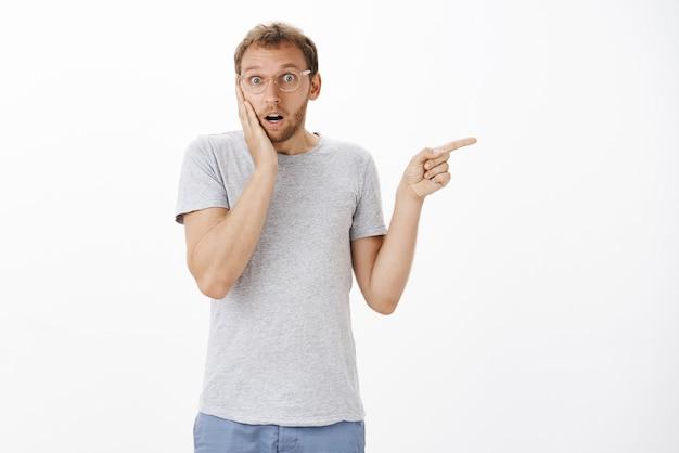 Porträt des betäubten niedlichen besorgten europäischen mannes in der brille, die handfläche auf wange von empathie hält und mit zeigefinger nach rechts zeigt