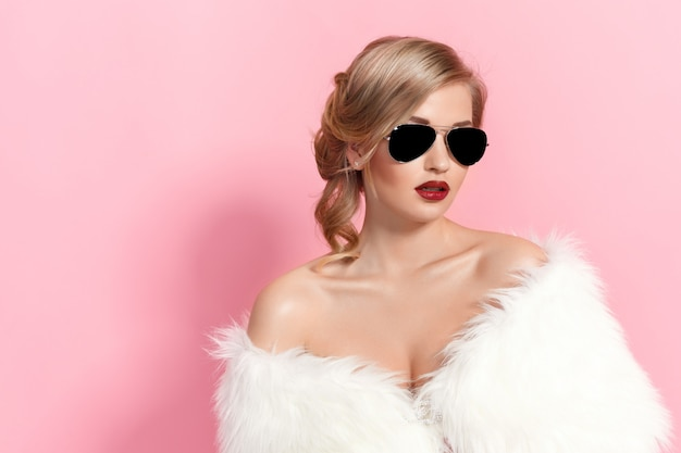 Porträt des bezaubernden mädchens im weißen pelz und in der sonnenbrille auf rosa. mode
