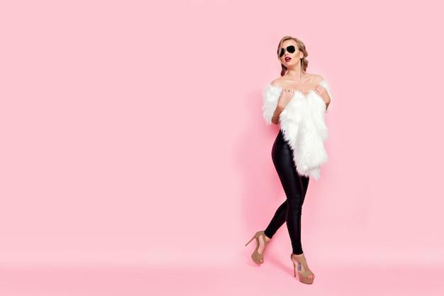 Porträt des bezaubernden mädchens im weißen pelz und in der sonnenbrille auf rosa.