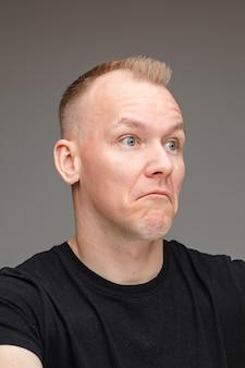Porträt des blonden kaukasischen mannes in schwarz, der mit unsicherem gesichtsausdruck wegschaut, der unsicherheit und verwirrung zeigt.