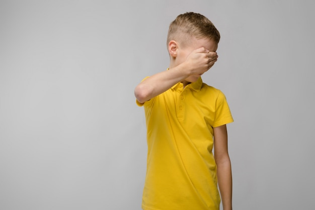 Porträt des blonden kaukasischen traurigen kleinen jungen im gelben t-shirt, das seine augen mit der hand schließt
