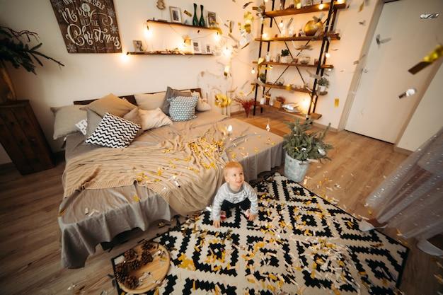 Porträt des blonden kleinen jungen im grauen pullover und in den schwarzen jeans, die auf teppich unter konfetti liegen und nach vorne schauen