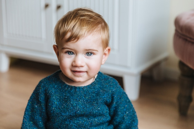 Porträt des blonden kleinen kindes mit prallen backen, untersucht mit blauen augen kamera