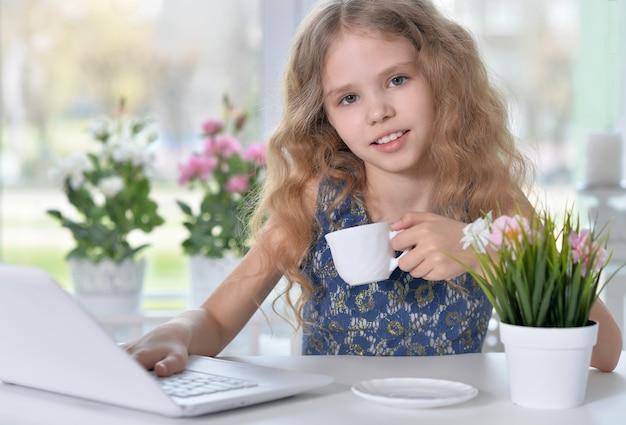 Porträt des blonden kleinen mädchens mit einer tasse mit laptop
