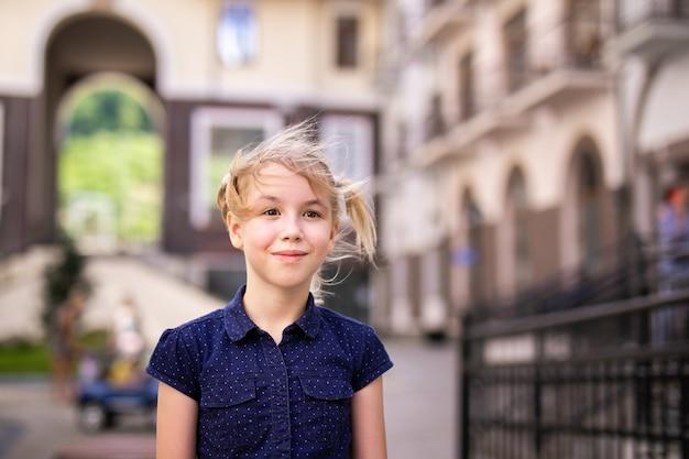 Porträt des blonden mädchens 10 jahre alt, spielend unter schönen alten häusern