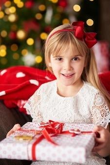 Porträt des blonden mädchens, das geschenk hält