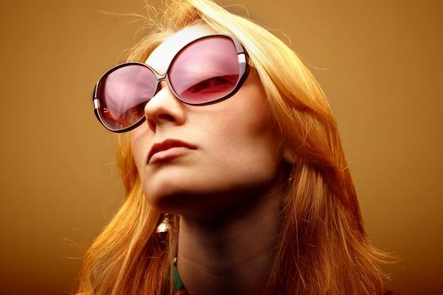 Porträt des blonden mädchens mit weinlesesonnenbrille