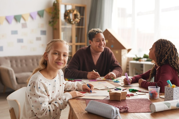 Porträt des blonden teenager-mädchens, das an der kamera lächelt, während kunst- und handwerksklasse in der schule, kopienraum genießt