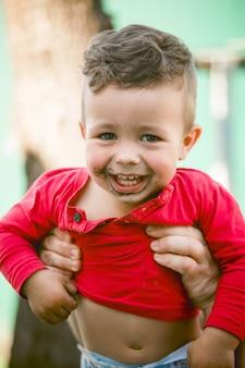 Porträt des boshaften gelockten kleinen jungen mit schmutzigem gesicht im roten t-shirt